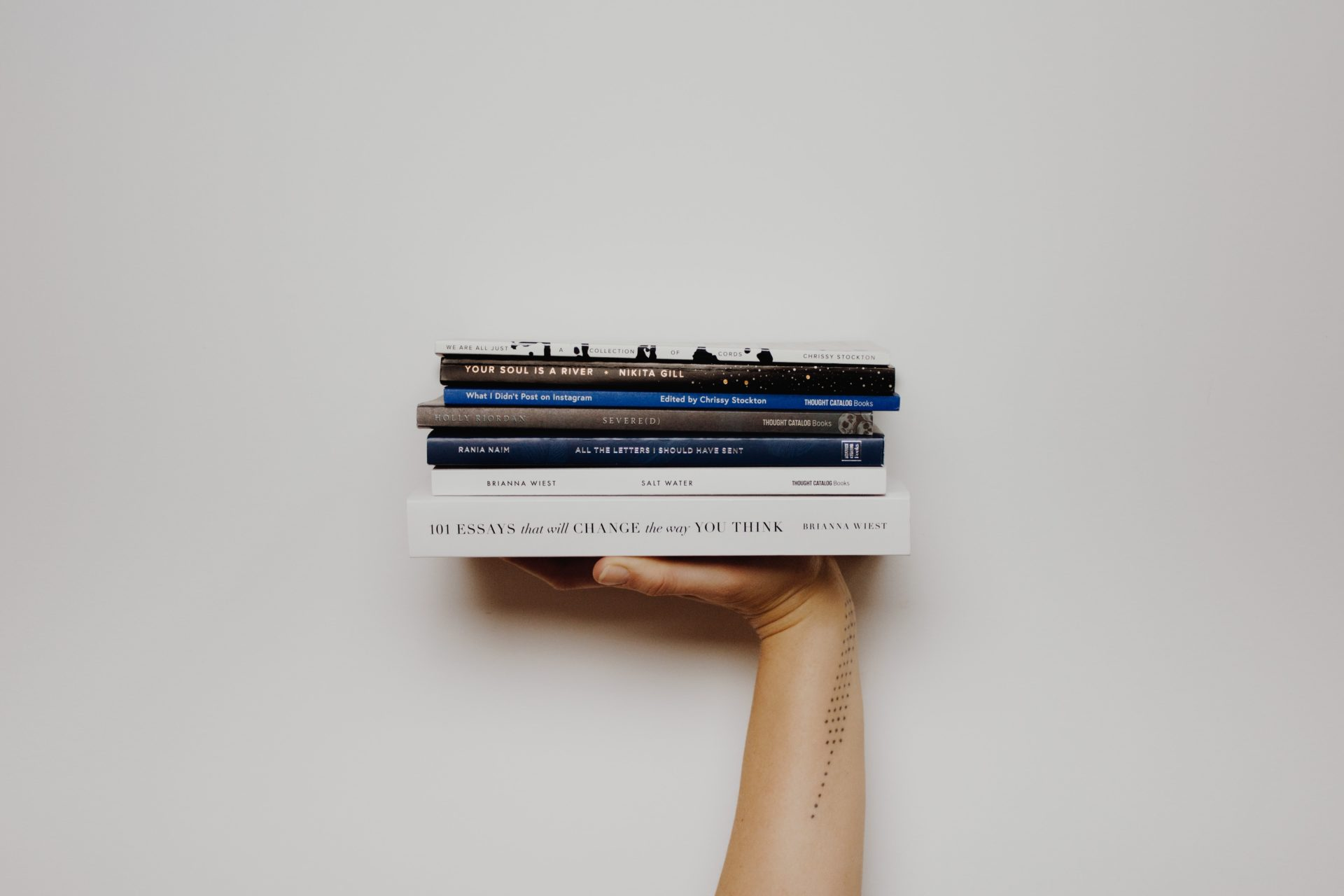 Hand holding a stack of books