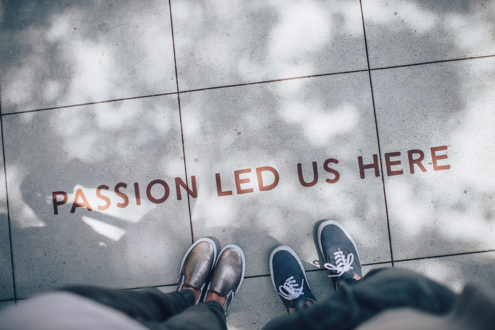 """Two people standing on tile paving. Text reads """"Passion Led Us Here."""""""