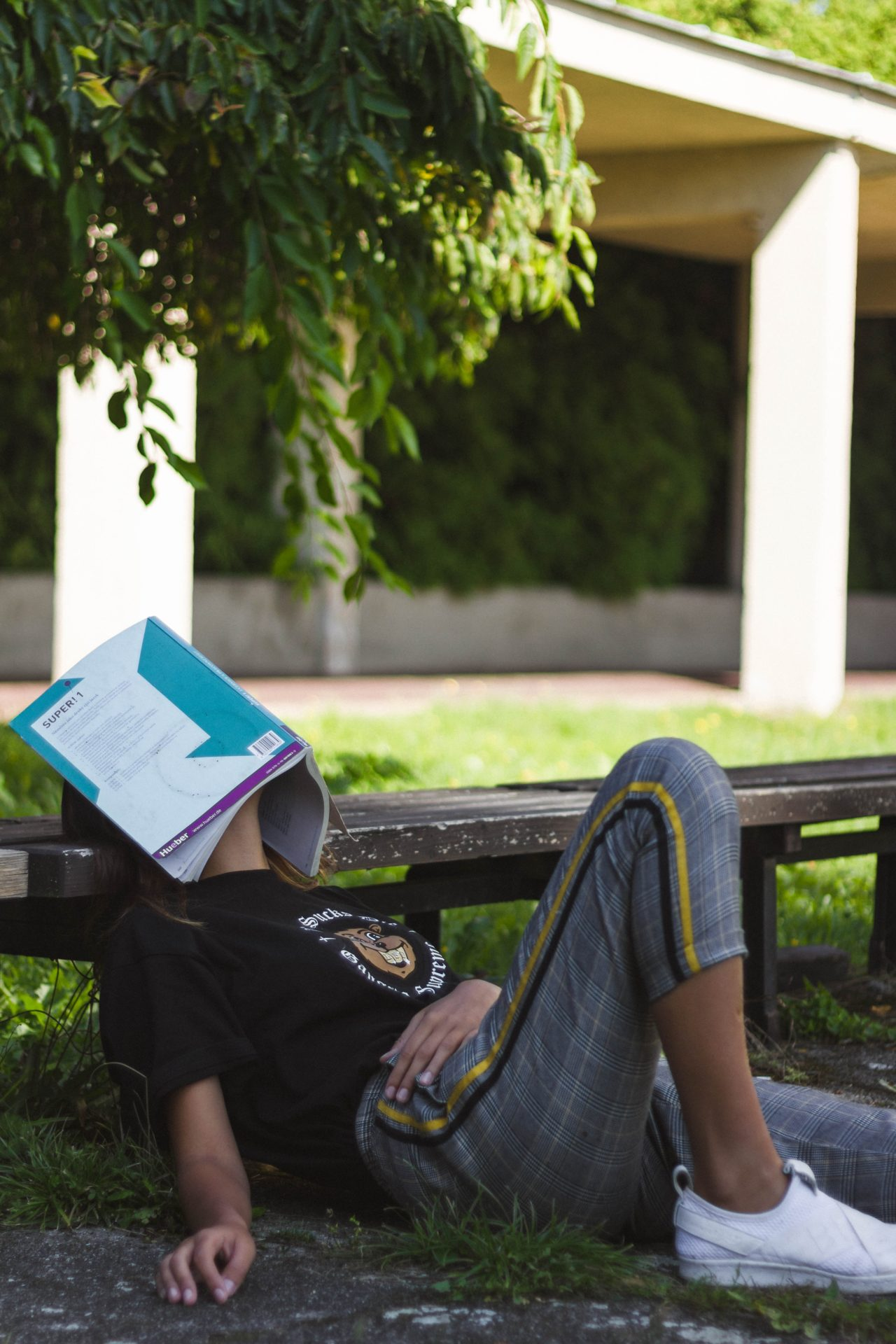 Person sitting with back on bench and book covering face, resting