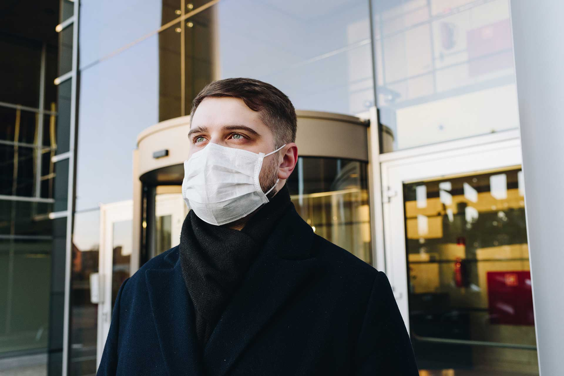 Person outside building wearing a face mask